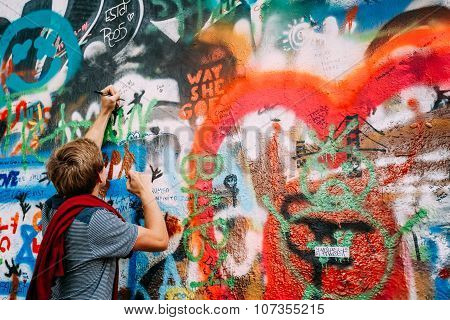 Woman draws on the John Lennon Wall in Prague, Czech Republic