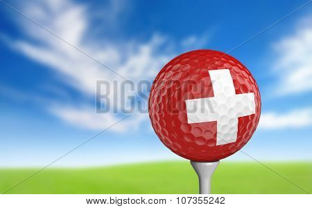 Golf ball with Switzerland flag colors sitting on a tee