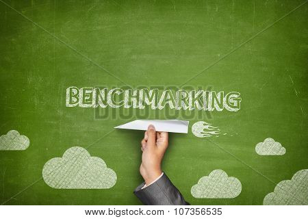 Benchmarking concept on blackboard with paper plane