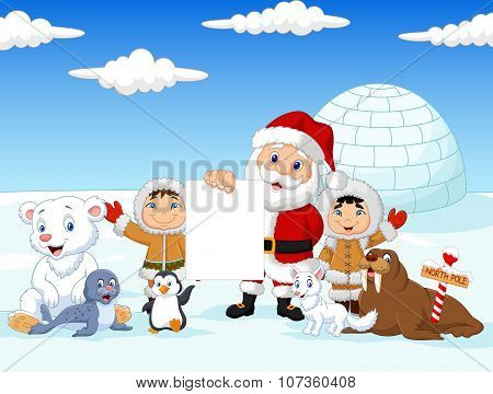 Santa claus holding blank sign with Little kids wearing traditional eskimo costume with arctic anima