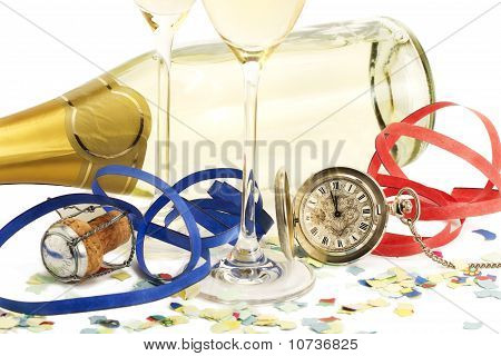 two glasses with champagne, old pocket watch, streamer, cork and confetti in front of a champagne bo
