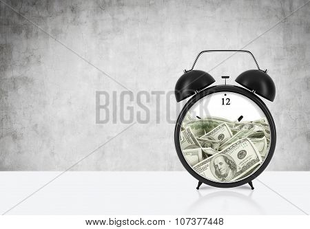 An Alarm Clock With Dollar Bills Inside Is On The Table. The Concept Of 'time Is Money' And A Time M