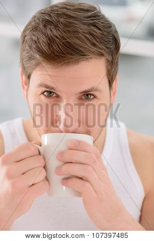 Attractive man in process of drinking coffee.