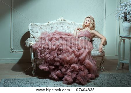Girl In A Magnificent Dress Sitting On The Sofa.