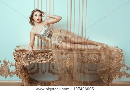 Fashionable Woman Lies On An Expensive Antique Table.