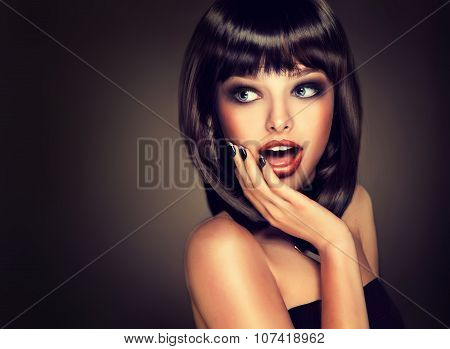 Surprised beautiful girl look away .Model brunette with hairstyle of the care.Black hair and nails