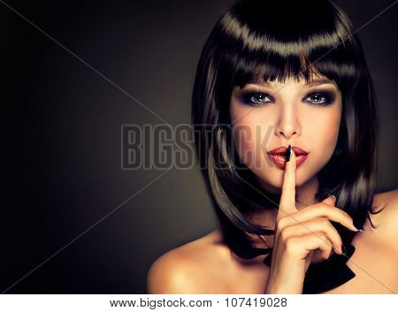 girl with a secret . Model brunette with hairstyle of the care. Black hair and a black manicure