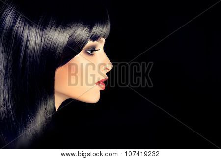 Girl in profile with black straight shiny hair and bangs .Model brunette with shiny hairstyle