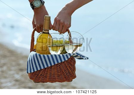 Young couple holding picnic basket with bottle of wine on sand beach