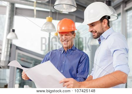 Cheerful male architects are discussing the new project