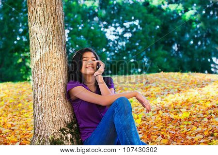 Teen Girl Sitting Against Autumn Tree Using Cell Phone