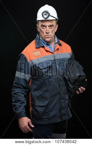 Coal miner showing lump of coal with thumbs up against a dark