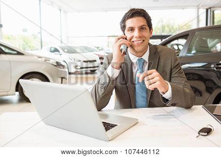 Smiling salesman having a phone call at new car showroom poster