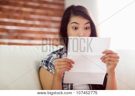Asian woman on the couch reading letter at home in the living room