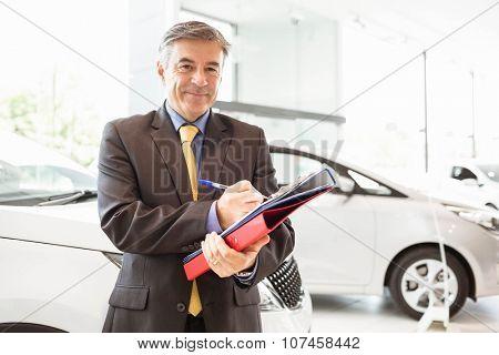 Smiling salesman writing on workbooks at new car showroom