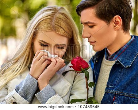 Upset girl  with cold rhinitis on autumn outdoor. Fall flu season. Man looks with compassion on suffering of loved one.