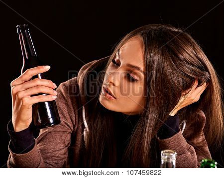 Drunk girl looking at bottle of alcohol. Soccial issue alcoholism.