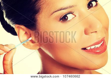 A young, beautiful, happy woman cleans her ear