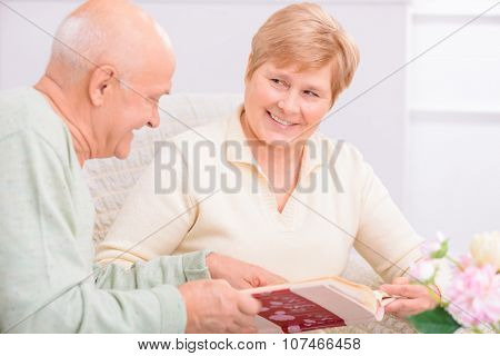 Sentimental love. Pleasant adult loving couple sitting in the arm chair and looking through photo album while having rest at home poster
