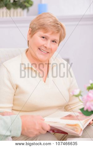 Full of happiness. Pleasant adult content woman sitting on the sofa and holding photo album while looking through it with her husband poster