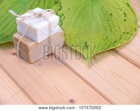Homemade organic soap tied with jute rope and two green hosta leaves with veins on the wooden planks poster