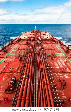 Crude oil carrier with pipeline in open sea.