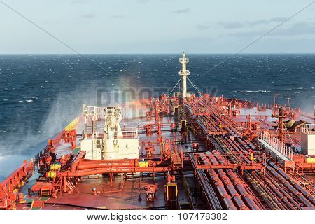 Ships bow and rainbow in spraying sea water.
