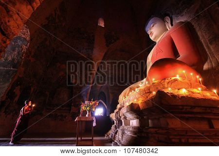 BAGAN, MYANMAR : Southeast Asian neophyte praying with candle light in a Buddihist temple in Bagan,