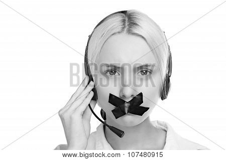 Sexy Young Blond Woman In A Headset Looking At The Camera And Can Not Speak, Because She Put A Plast