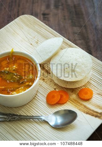 Spicy and tangy rasam with idli. Popular South Indian small meal.