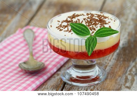 Traditional English strawberry trifle in transparent dessert glass on rustic wooden surface
