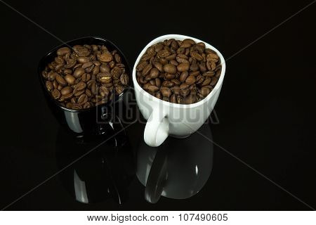 Two Cups Filled With Coffee Beans On A Black Background With A Pronounced Mirror Image.