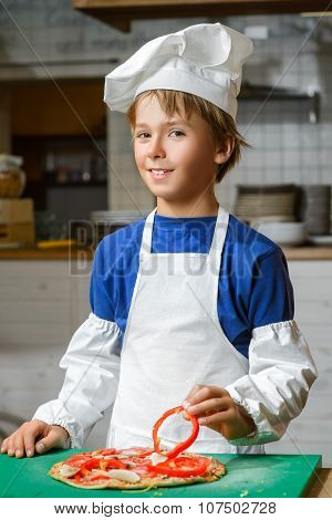 Funny happy chef boy cooking at restaurant kitchen and make pizza