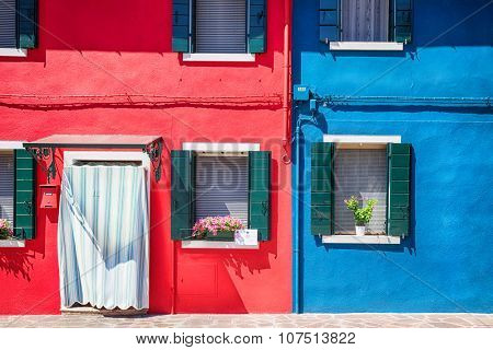 Colourfully painted house facade with windows on Burano island, province of Venice, Italy