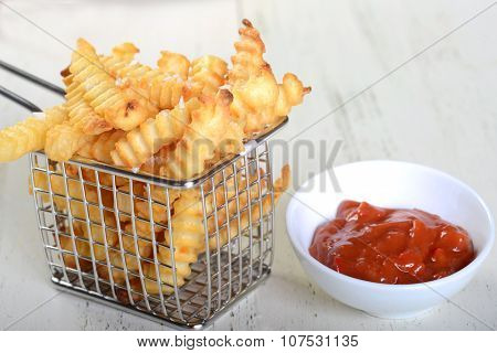 Crispy French Fries in a wire fryer basket with a spicy red pepper aoli