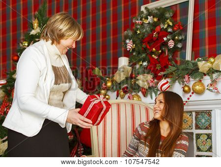 Portrait of a grandmother and teen granddaughter near the Christmas tree being happy and joyful poster