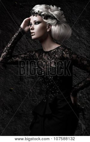 Beautiful girl in gloomy image with white wig, unusual hairstyle, black dress and dark makeup. Art b