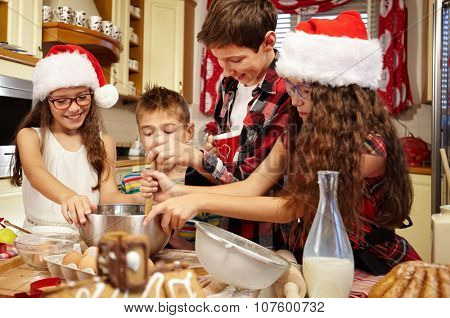 Happy family preparing christmas pastries and cake together