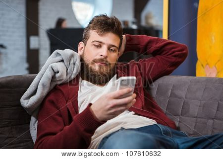 Relaxed young handsome attractive man lying grey on sofa and using cellphone
