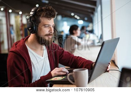 Concentrated handsome male with beard using headset and laptop