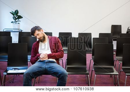 Bearded guy in brown hoodie and blue jeans sitting and sleeping in conference room
