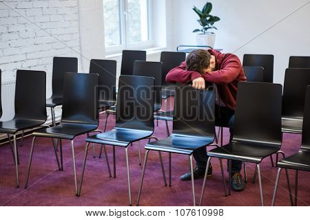 Tired young man holding gasses and snoozed in conference room poster