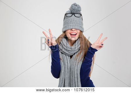 Portrait of a happy woman covering her eyes with hat and showing peace sign isolated on a white background