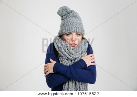 Portrait of a freezing woman in winter cloth standing isolated on a white background