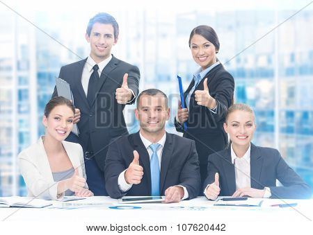 Group of thumbing up business people working at the table, blue background. Concept of teamwork and cooperation