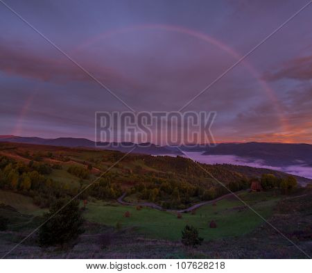 Rainbow At Sunrise In Mountains