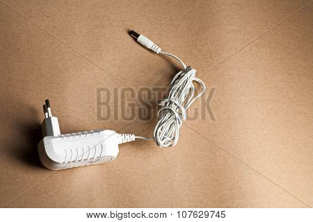 Laptop AC adapter on brown craft paper with copyspace poster