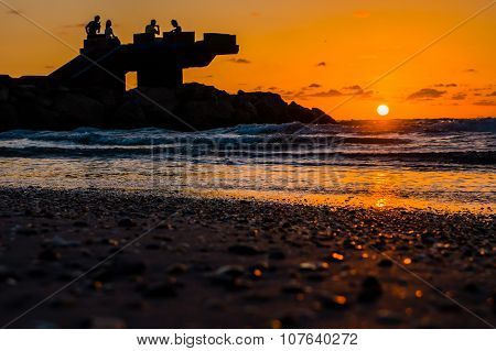Sillhouette of people in the beach during sunset