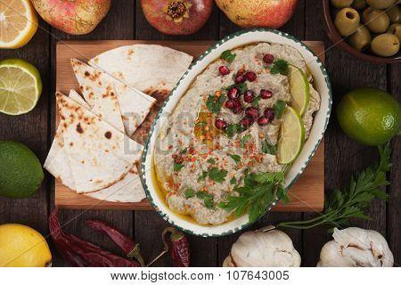 Baba ghanoush, levantine eggplant dip served with   pita bread, lime slices and pomegranate