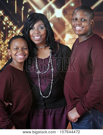 An attractive African American family happily standing outside a bright, Christmas-lit mall.
